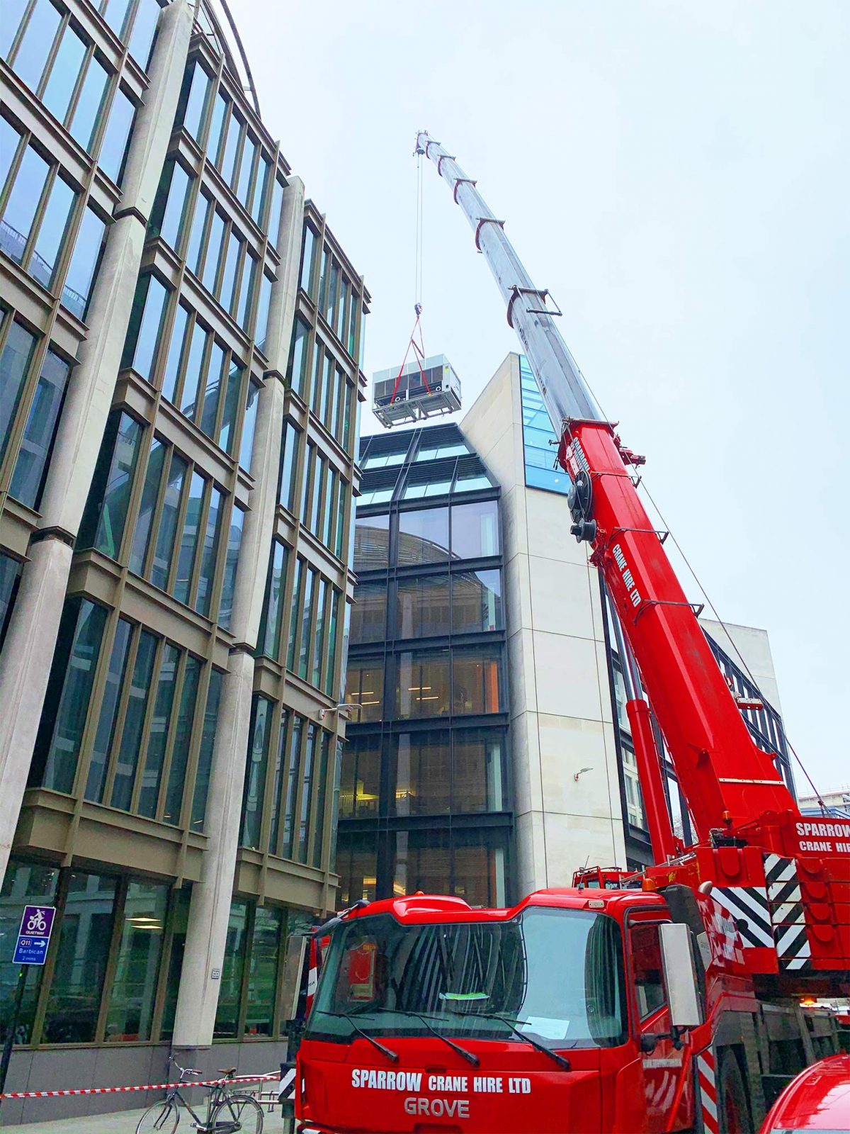 Grove GMK5250L lifting an air con unit on to a building in Gresham St. City of London